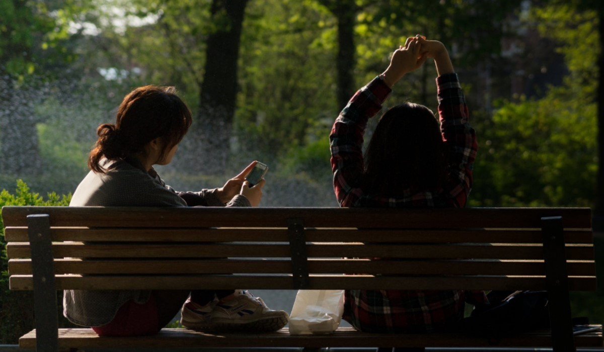 deux personnes assises sur un banc avec leur smartphone en main