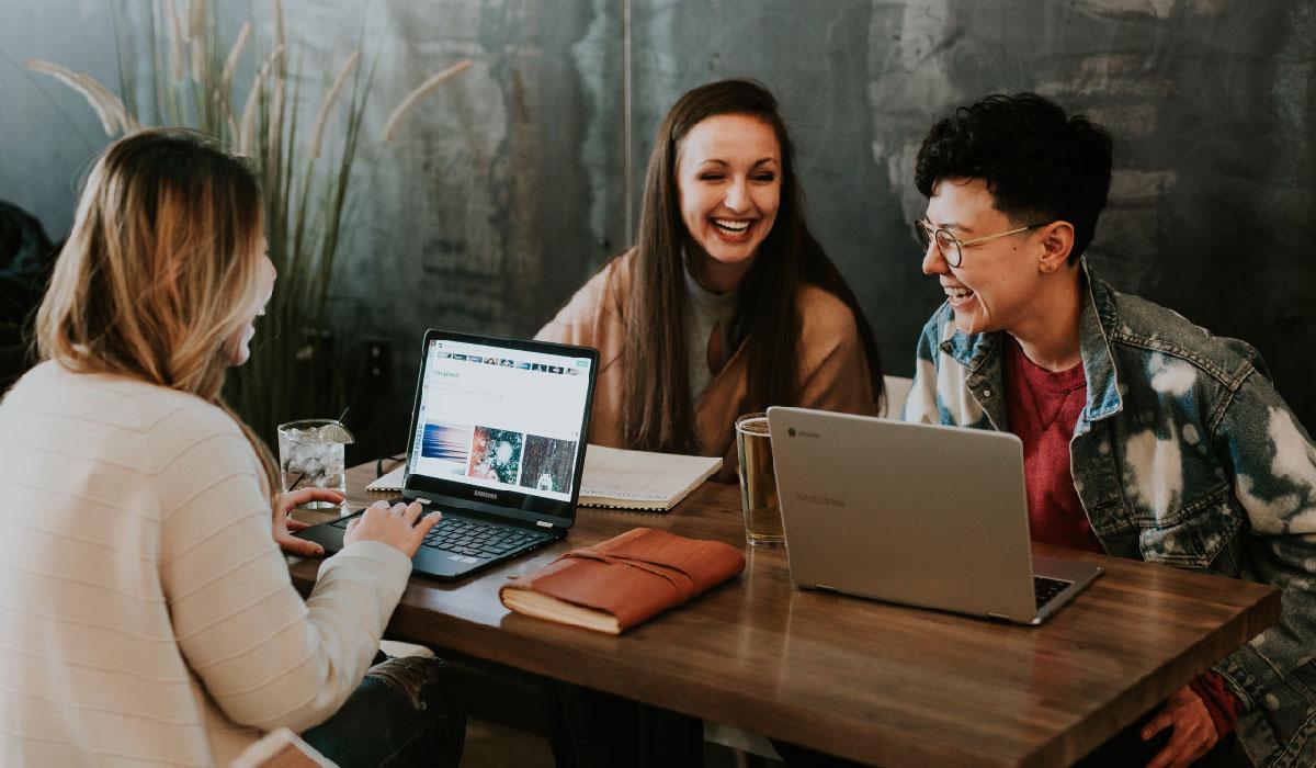 3 femmes rient, assises autour d'une table en naviguant sur internet