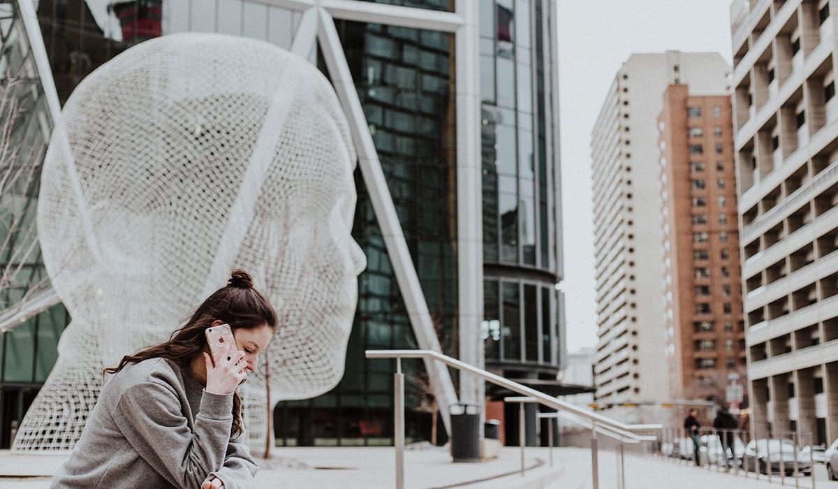 jeune femme sur la place centrale d'une grande ville en train de téléphoner