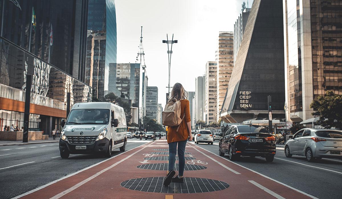 jeune femme avec un sac à dos marchant au milieu d'une avenue
