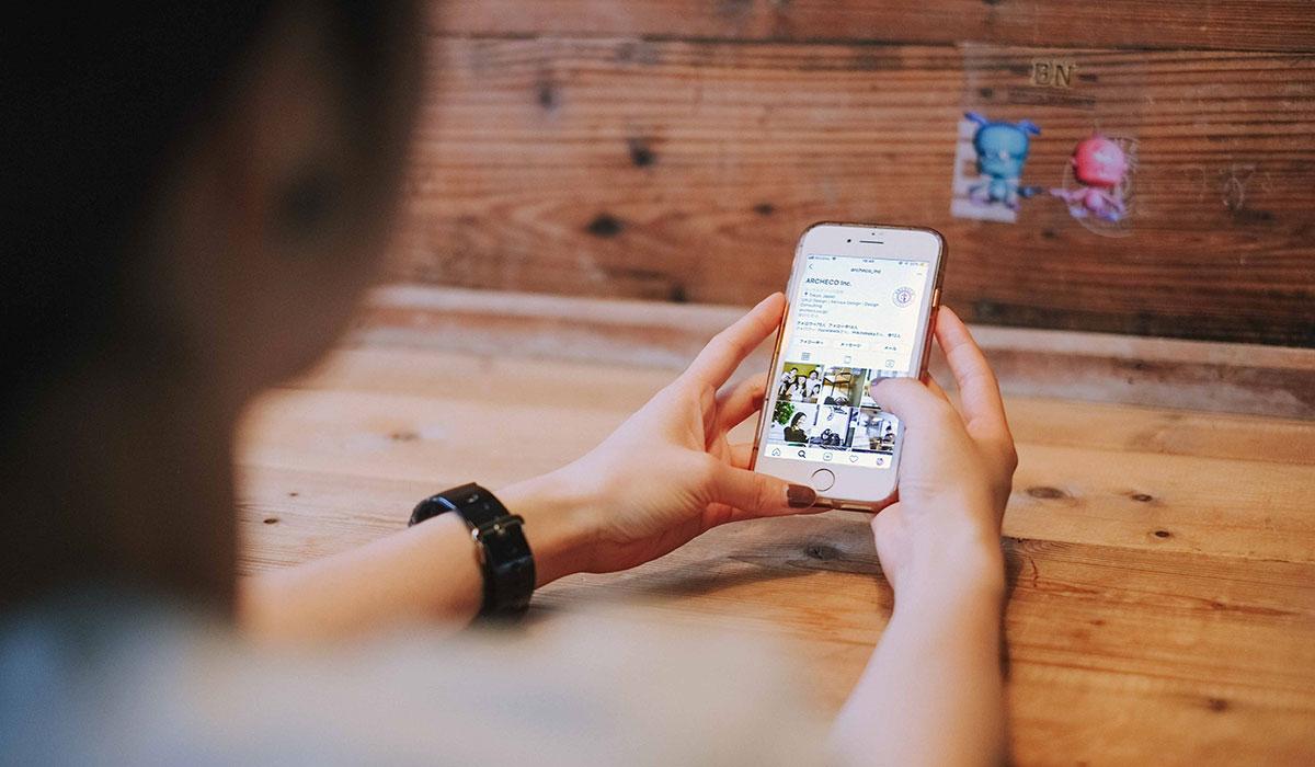 Jeune femme assise à table vue de dos, naviguant sur son téléphone portable