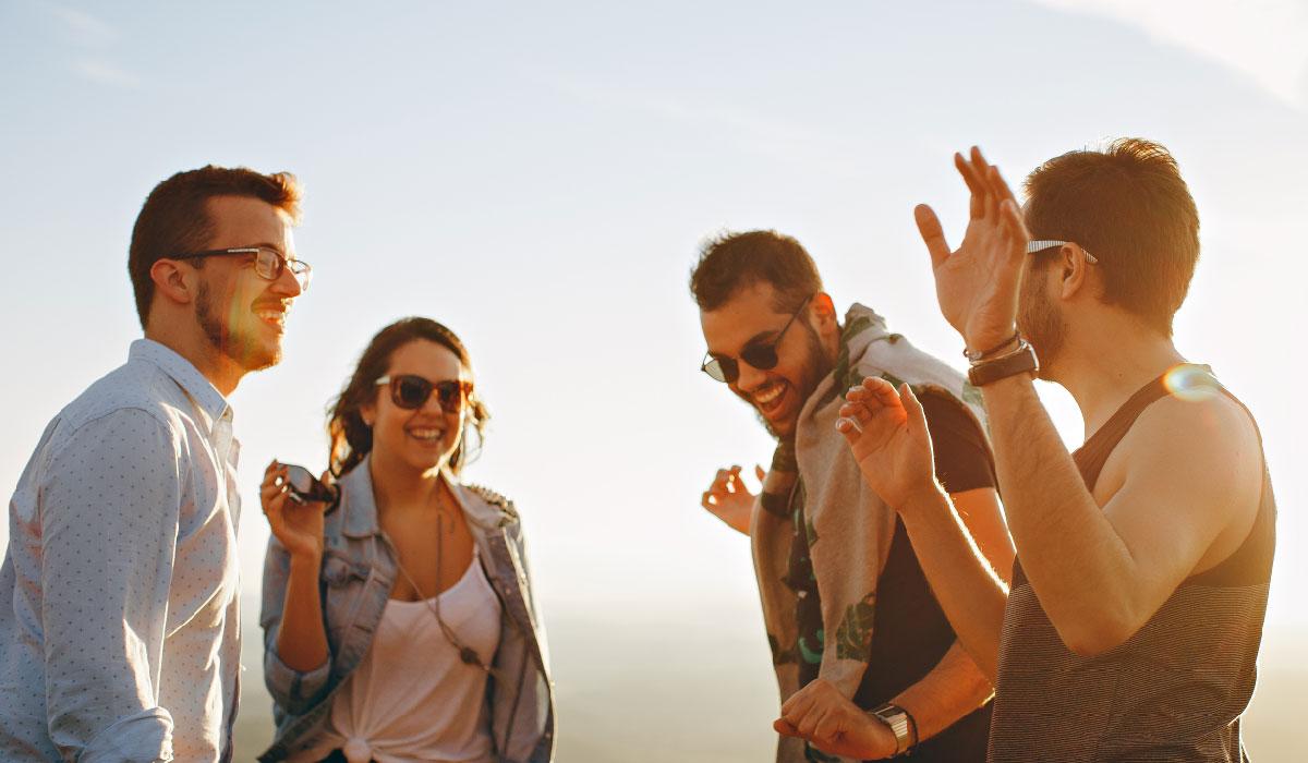 une jeune fille et trois jeunes garçons dansent au crépuscule sur la plage