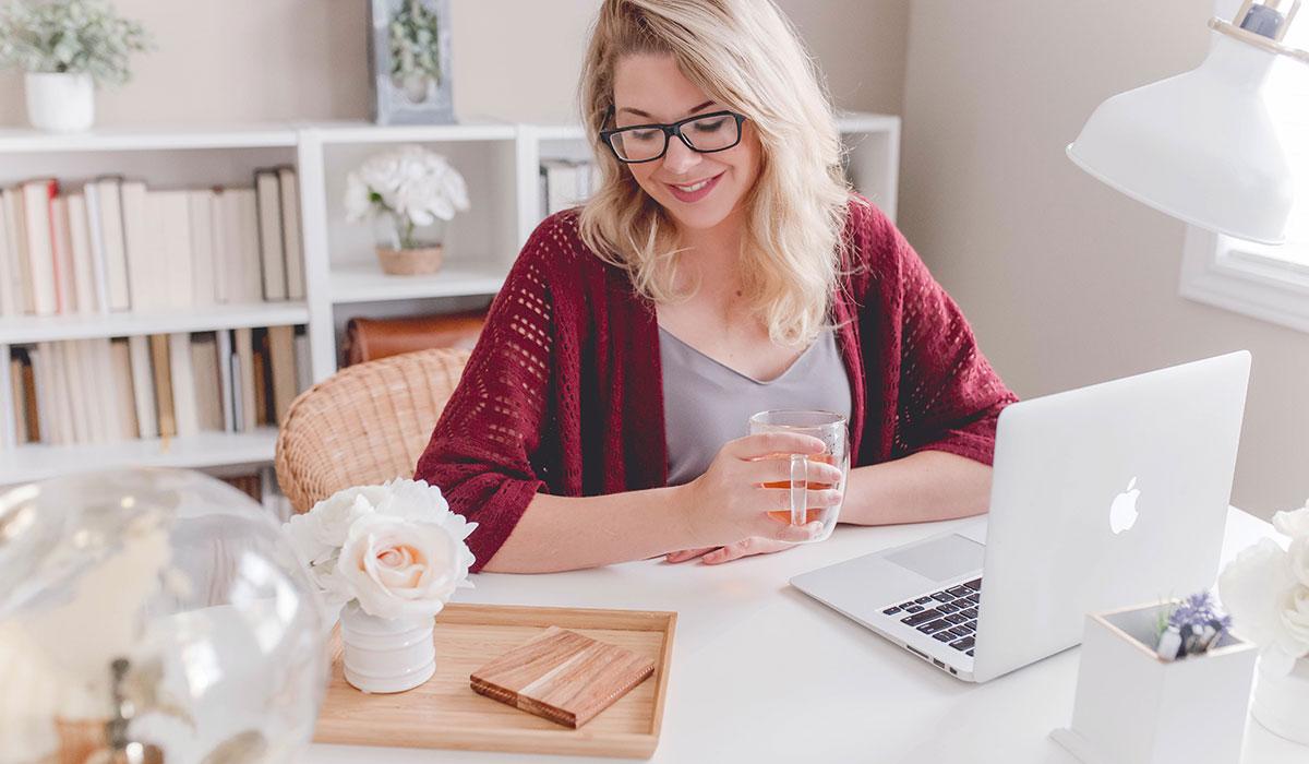 jeune femme assise à son bureau qui boit une tasse de thé