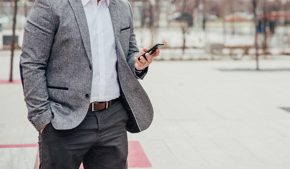 Homme en costume gris tenant un téléphone dans la rue