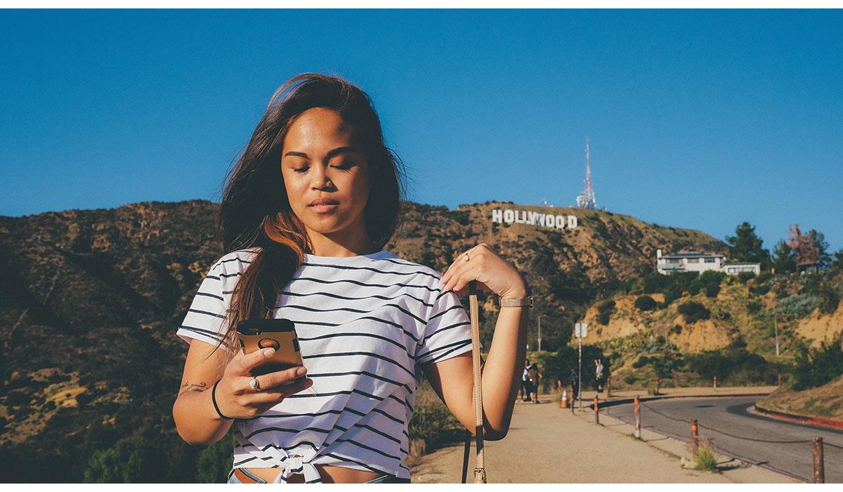 jeune fille regardant son téléphone portable au bord de la route