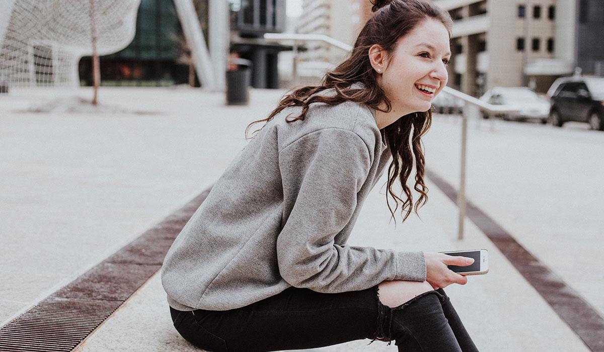 jeune fille assise sur les marches d'une place à l'exterieur