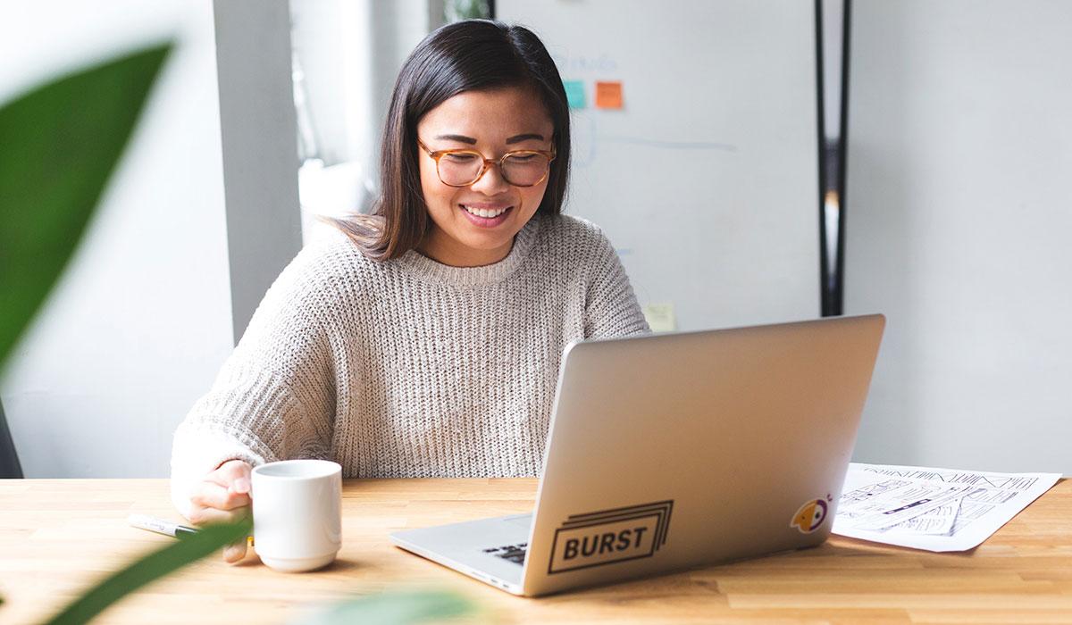 jeune femme assise à une table qui navigue sur son ordinateur portable