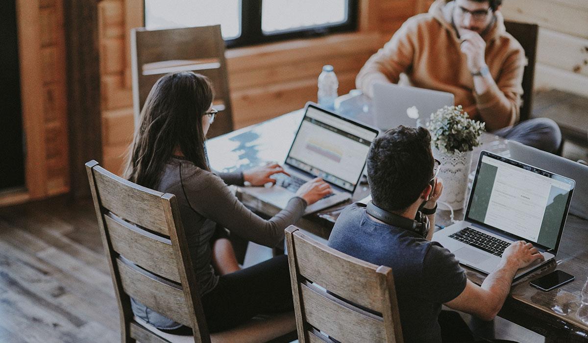 3 personnes sont assises autour d'une table et travaillent sur leur ordinateur portable