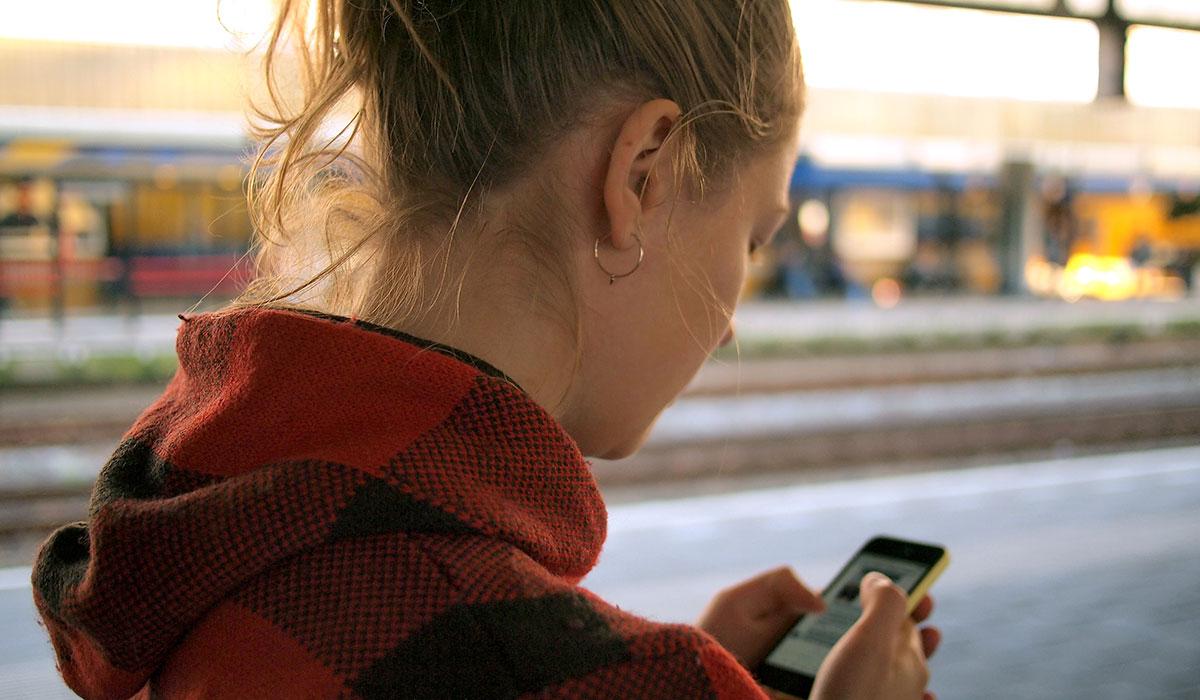 jeune femme sur un quai de gare qui regarde son téléphone