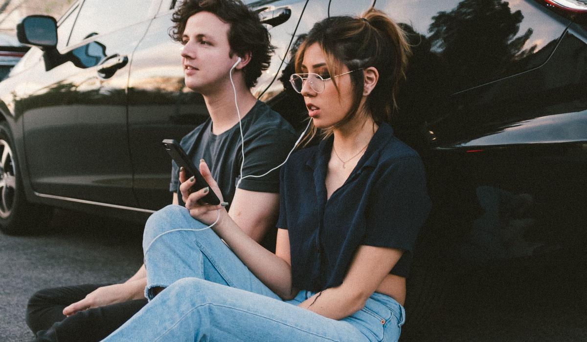 un garçon et une fille écoute de la musique sur leur téléphone adosser à une voiture noir.