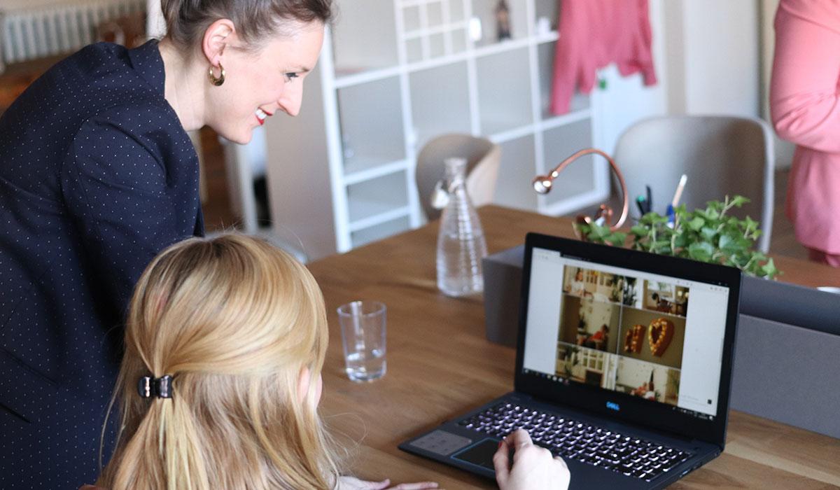 Deux jeunes femmes discutent devant un ordinateur portable