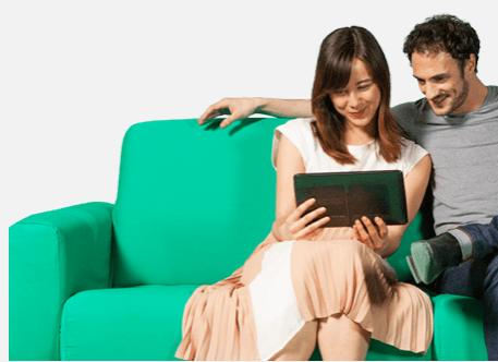 Couple sur un canapé vert qui regarde sur une tablette