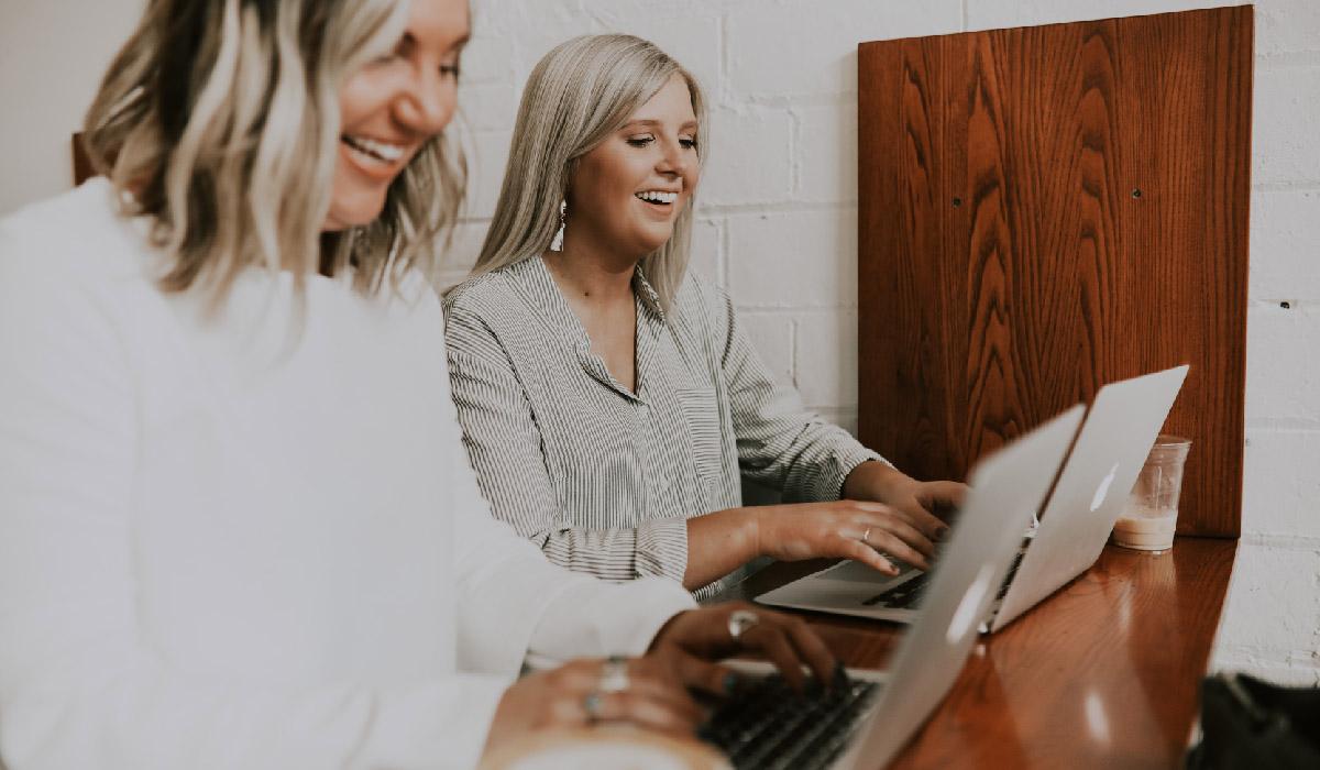 deux femmes riant devant leur ordinateur