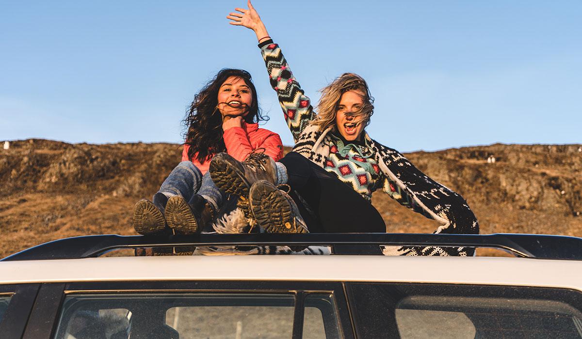 deux jeunes femmes assises sur le toit d'une voiture