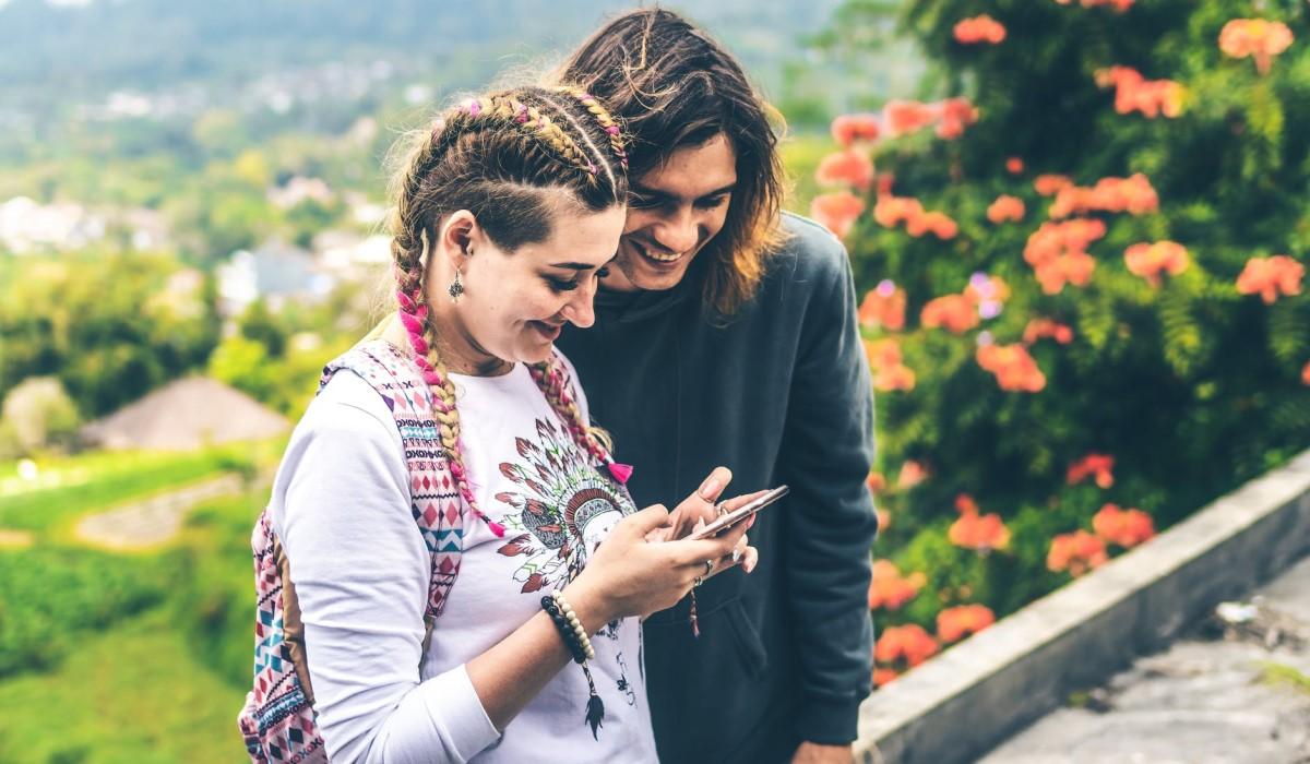 Un jeune couple avec leur smartphone en main