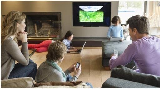 une famille qui utilise plusieurs équipements TV, smartphone, PC.... dans leur salon