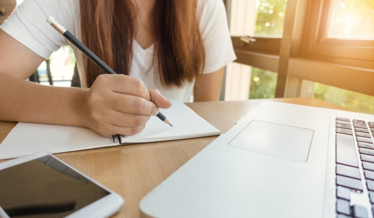 jeune femme qui prend des notes près de son smartphone et pc