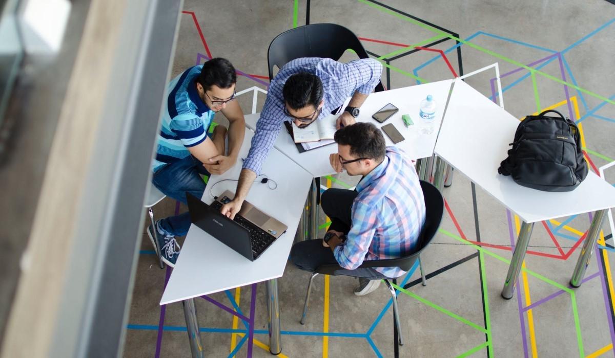 des personnes assis connectes sur leur pc et Smartphone