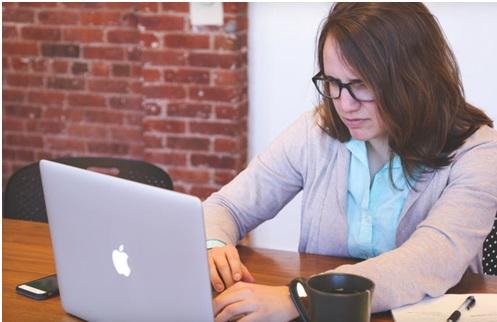 Une personne surprise devant son écran d'ordinateur