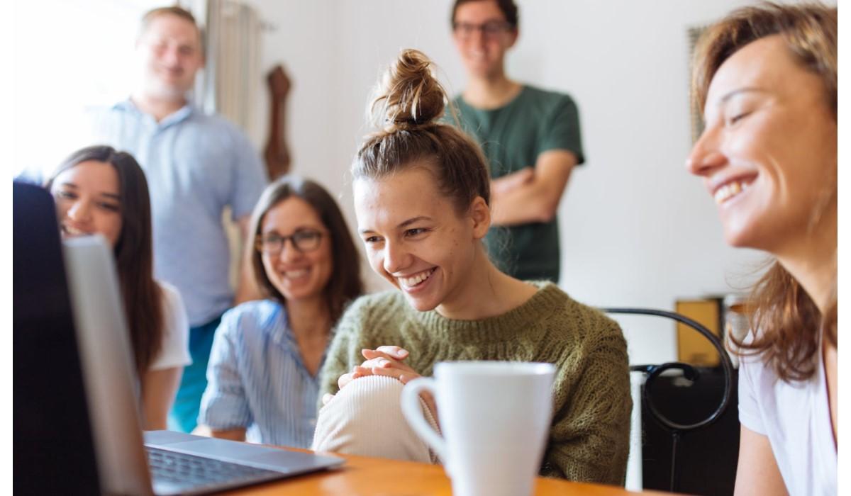 un groupe de personnes content fixant un ordinateur