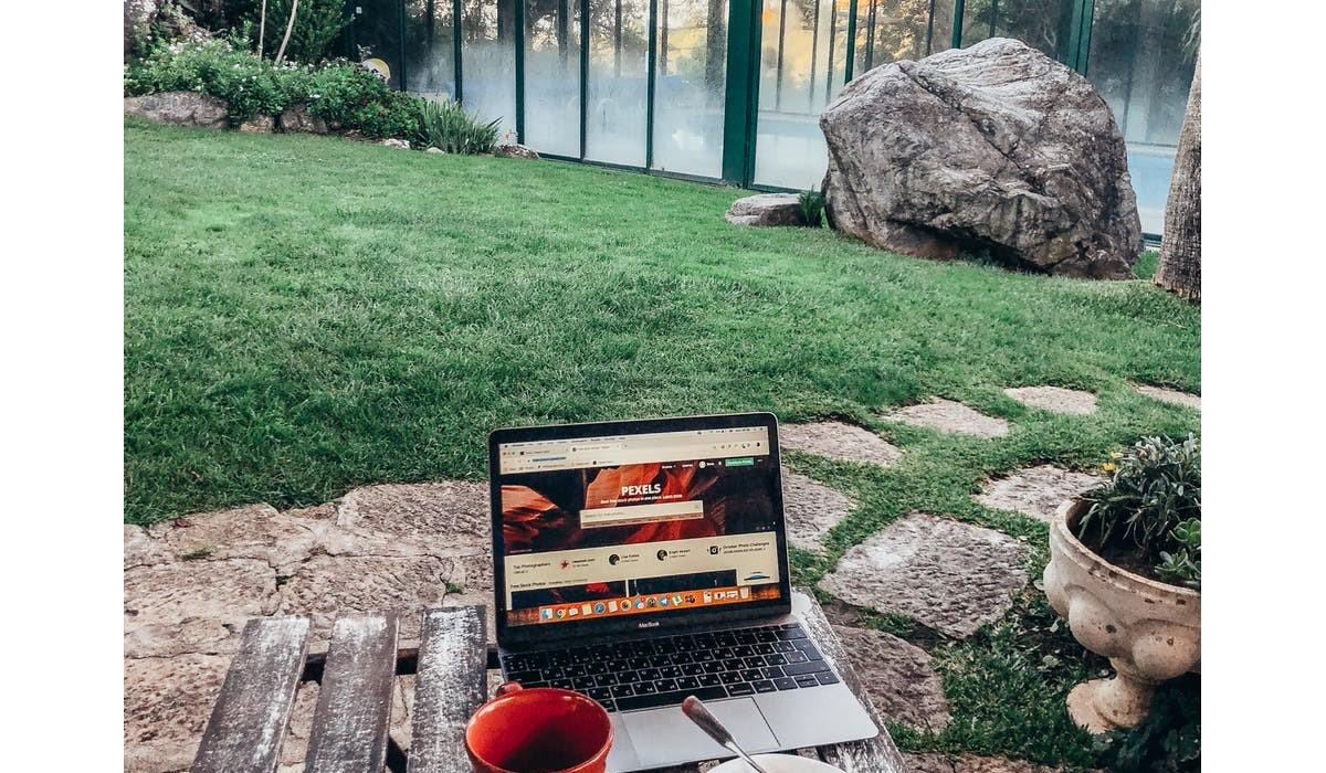 personne qui utilise son ordinateur dans son jardin