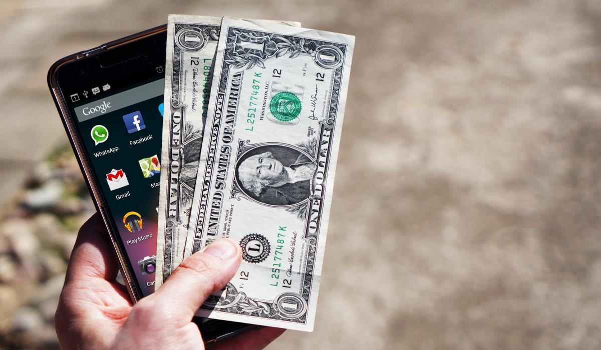 smartphone avec deux billets pris en main