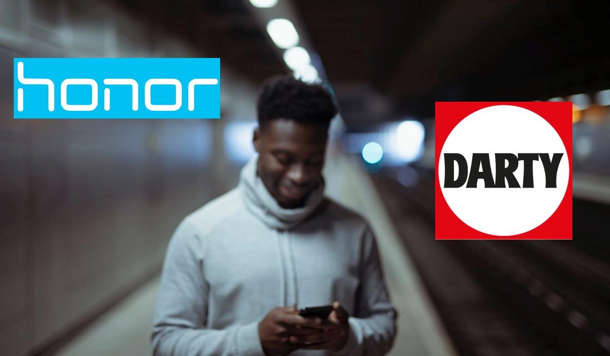 photo d'un homme qui tient son smartphone sur le quai d'une gare avec le logo honor et darty