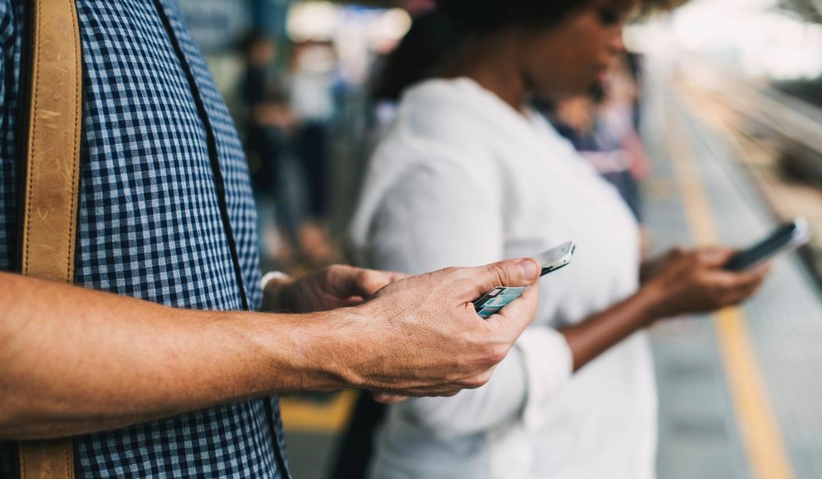 Deux personnes qui surfent sur leur smartphone en attendant le métro