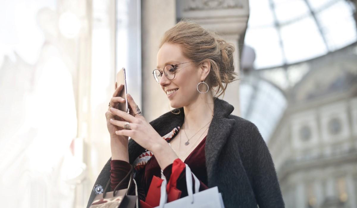 une femme qui utilise son smartphone avec des sacs de shopping à la main