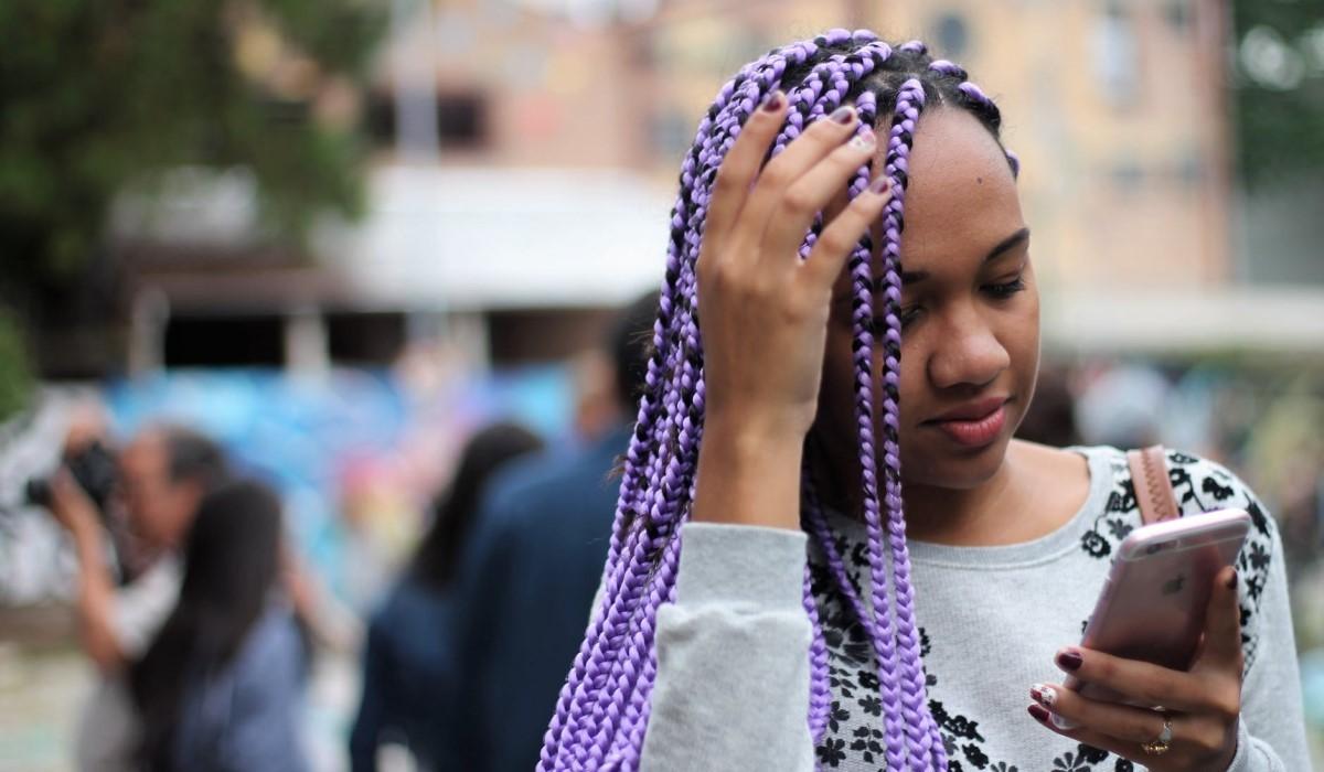 une jeune femme qui consulte son smartphone en marchant