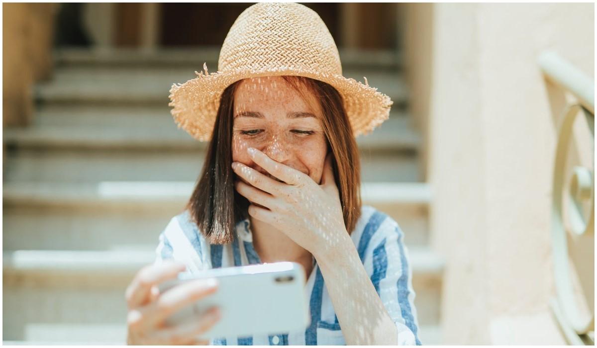 jeune fille contente avec son smartphone en main