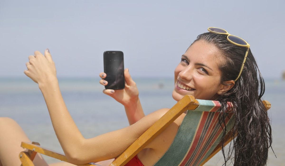 jeune femme assise sur un transat a la plage avec son smartphone en main