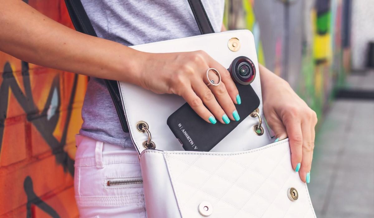 jeune femme qui glisse son smartphone dans son sac a main