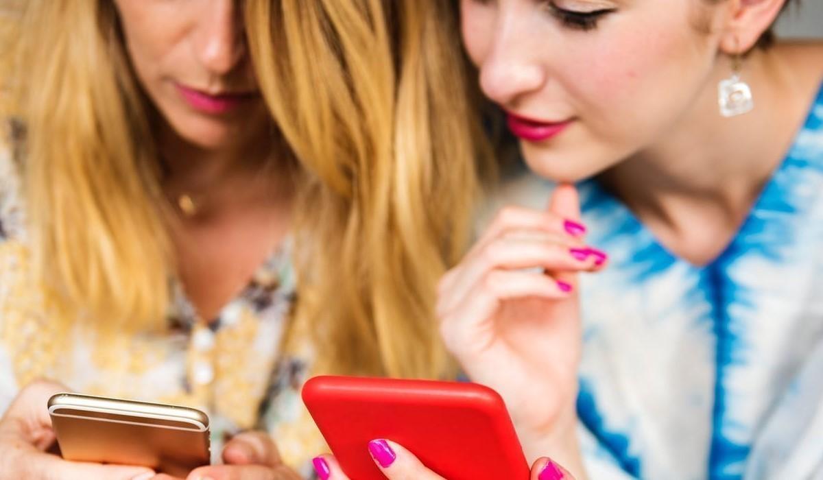 Deux jeunes femmes qui surfent sur leur smartphone