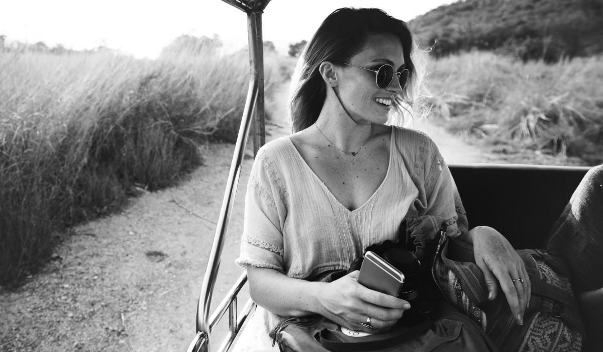 jeune femme en voyage avec son smartphone en main