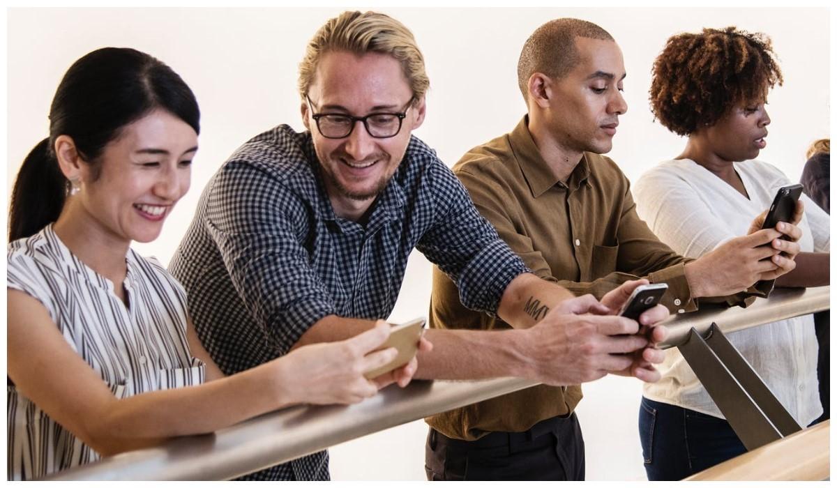 quatre personnes alignés avec leur smartphone en main