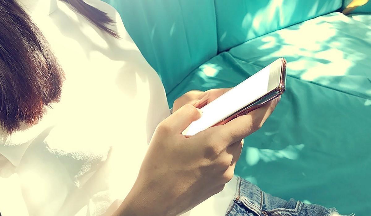 une jeune femme qui surf sur son Smartphone