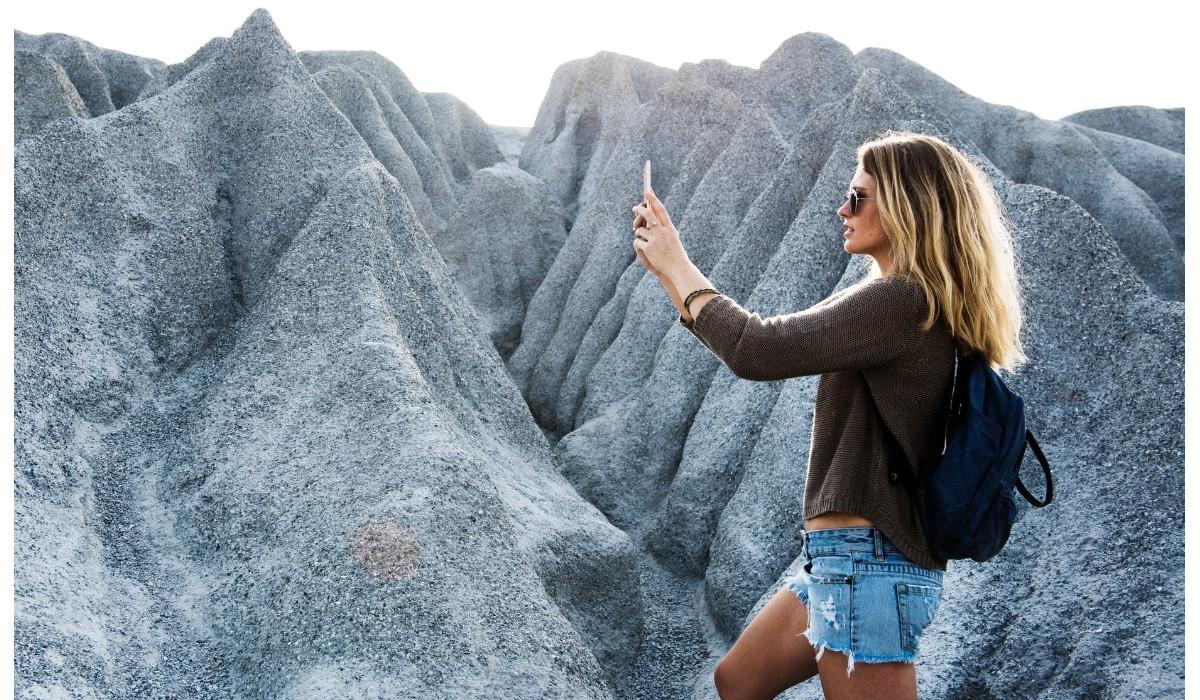 une femme qui utilise son smartphone en vacances
