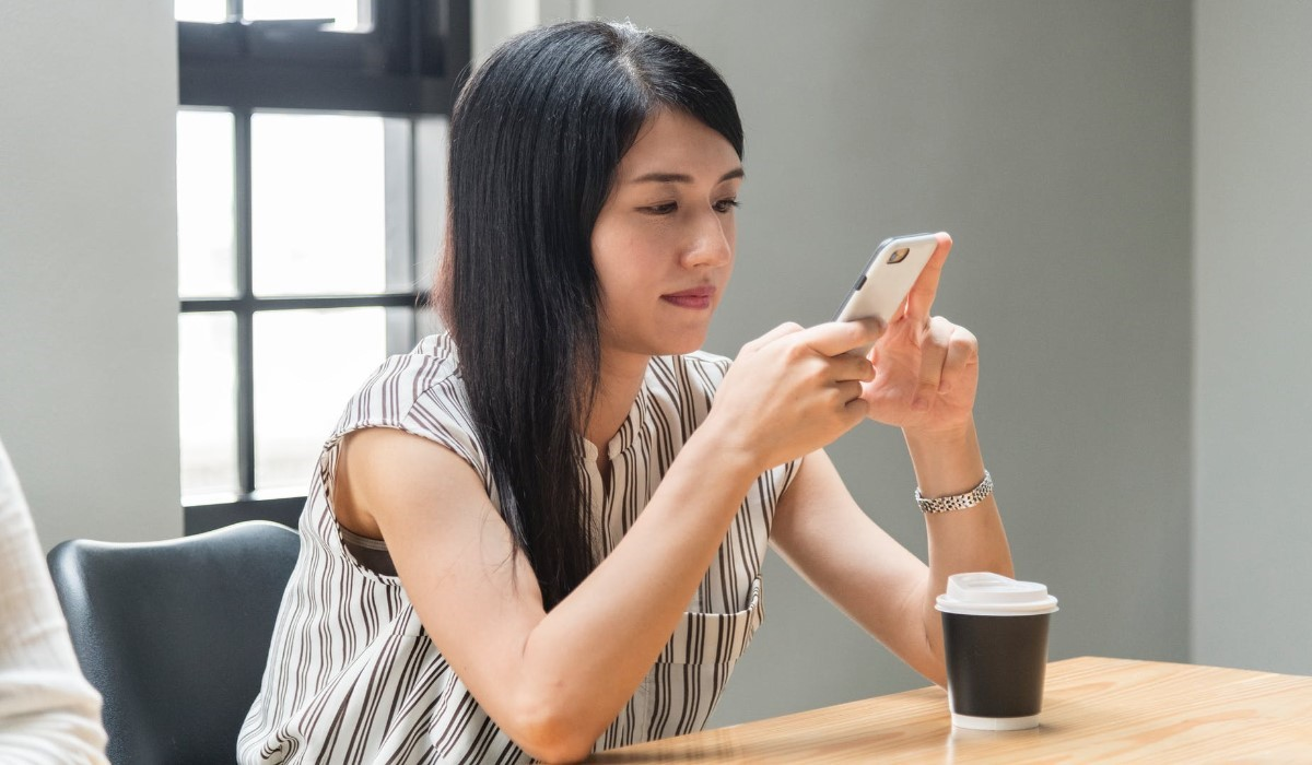 femme assise qui consulte son smartphone