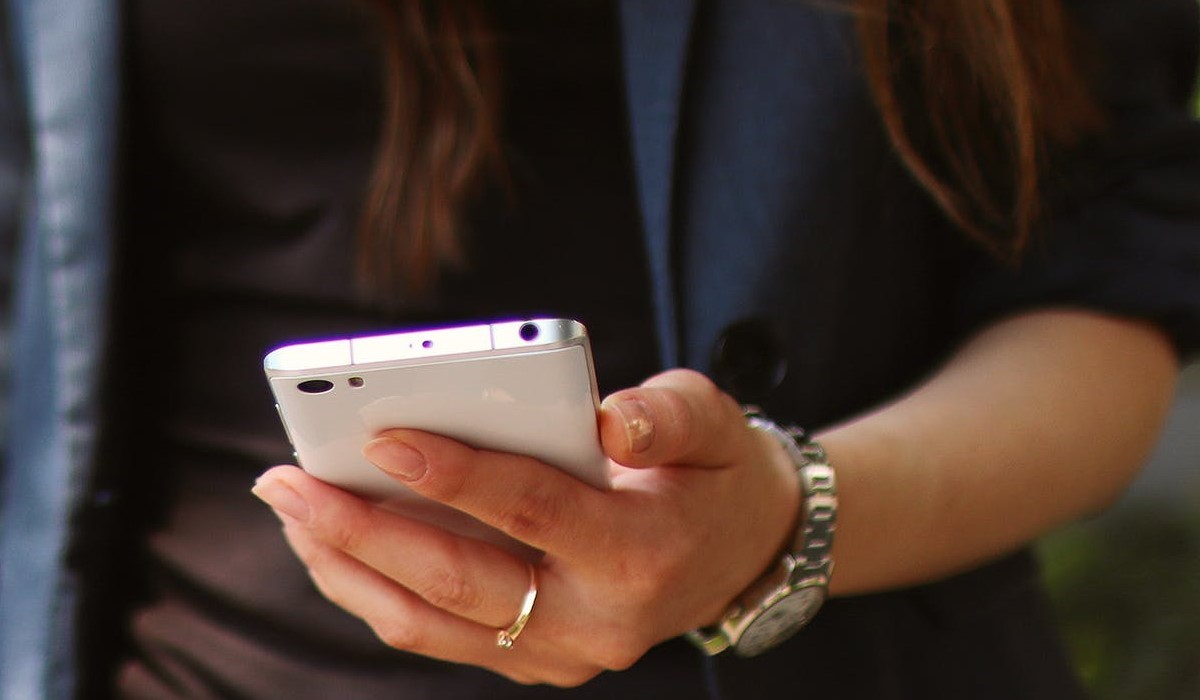 femme contente qui consulte son smartphone
