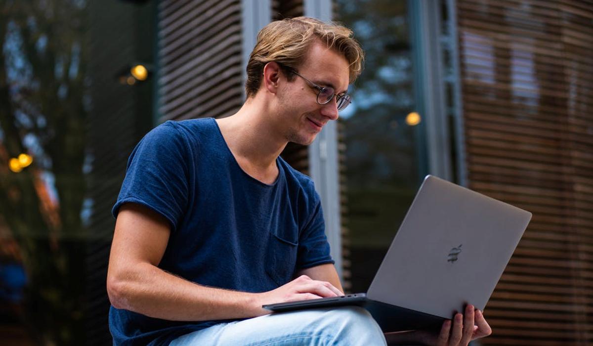 homme assis avec son ordinateur sur ses genoux