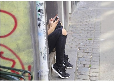 Une ado assise dans la rue avec son smartphone