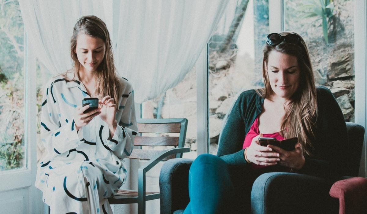 deux jeunes femmes assises avec leur Smartphone