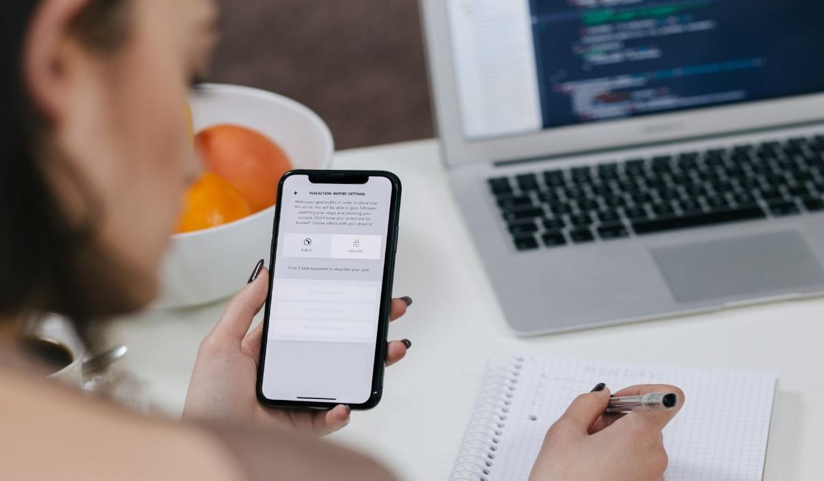 une femme qui prend des notes avec son smartphone en main et son pc posé sur un bureau