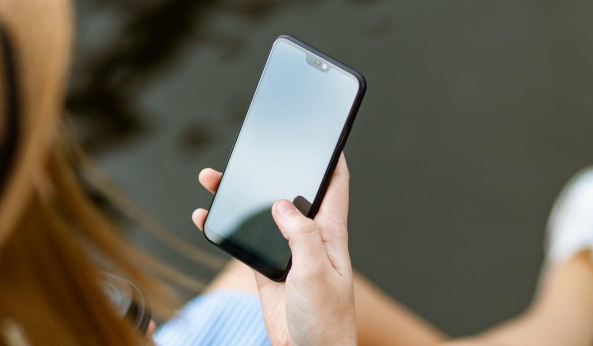 une femme assise avec son smartphone en main