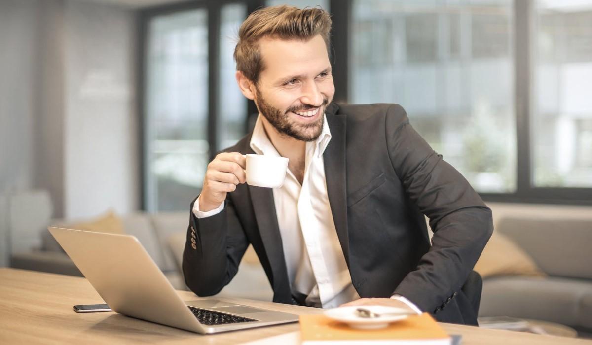 un homme assis avec son ordinateur posé sur un bureau