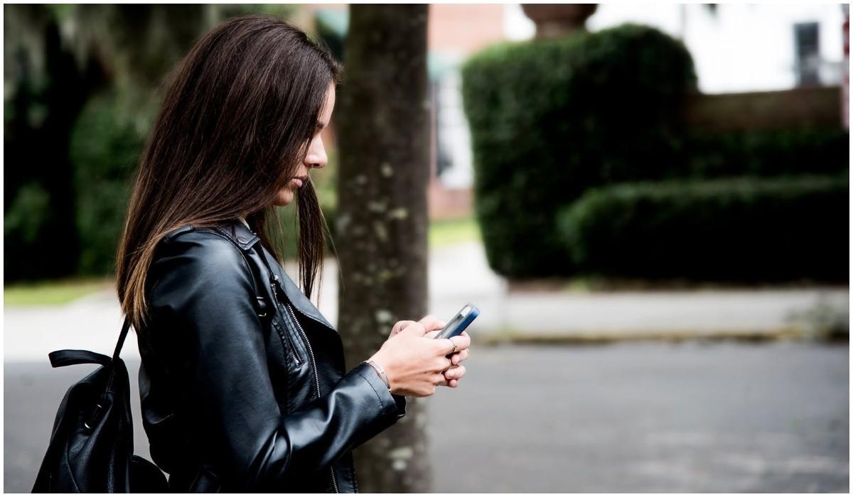 jeune femme debout qui surf sur son smartphone