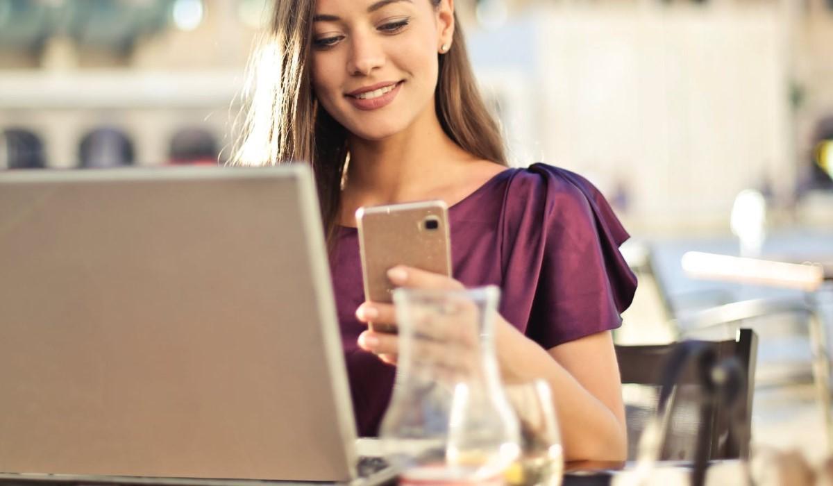 jeune femme qui utilise son mobile et son pc