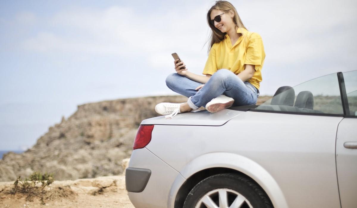 jeune femme assise sur le capot d'une voiture avec son smartphone en main