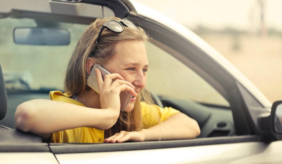 jeune femme au téléphone assise sur le siege passager d'une voiture
